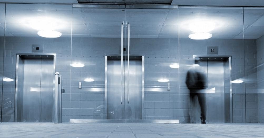Hombre esperando en rellano ante la puerta de tres ascensores